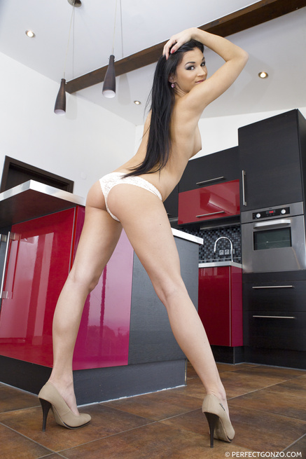 Busty brunette gets on a kitchen counter and starts furiously masturbating