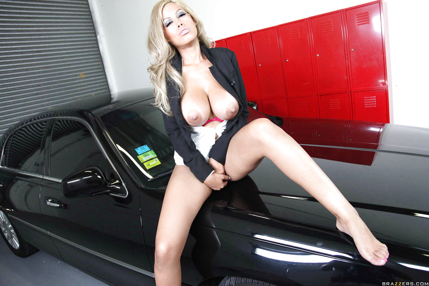 Busty blonde seduces a guy with her massive tits in a garage