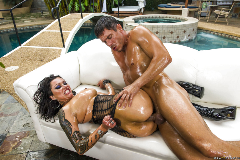 Tattooed brunette is masturbating and fucking next to the pool