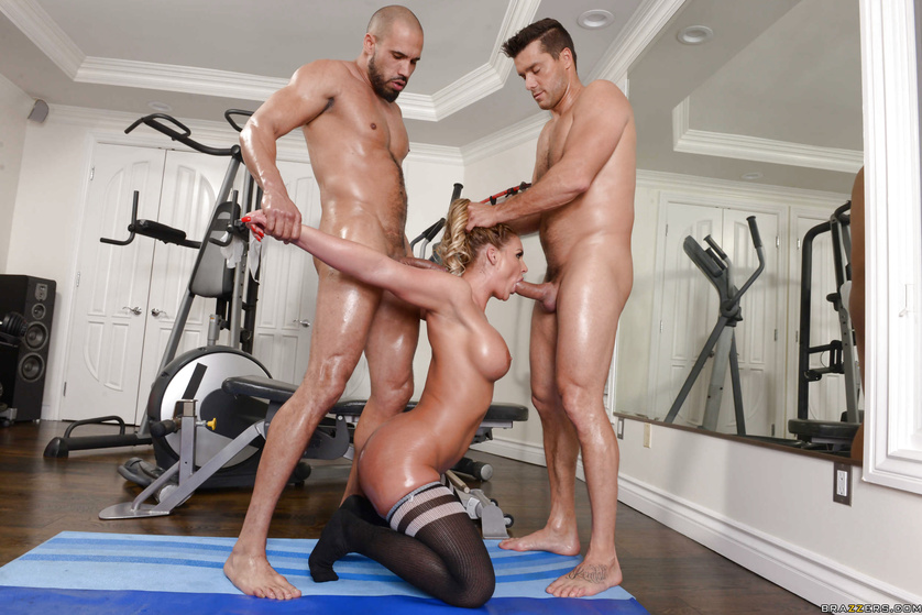 Muscular men are banging the flexible model in the gym