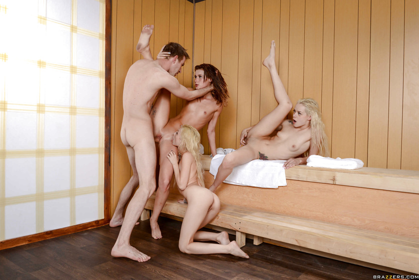 Three hot babes are fucking with the strong man in the sauna