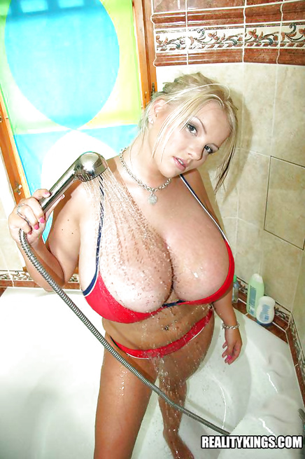 Tattooed blonde is touching her wet boobs on camera