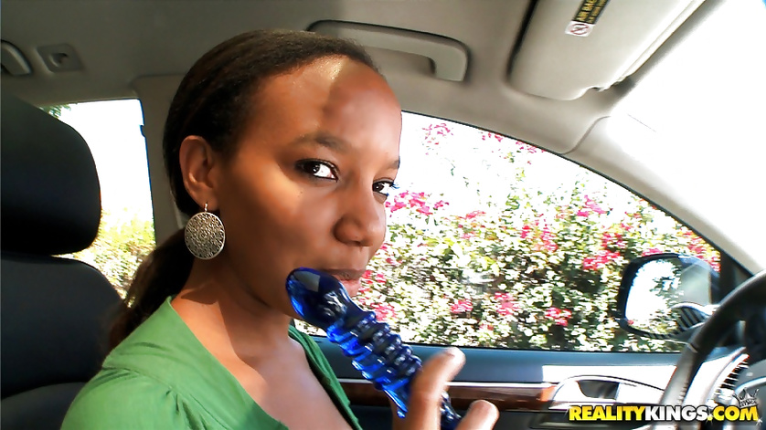 Ebony brunette is playing with blue dildo in the car