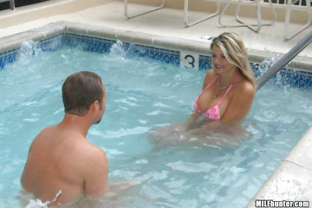 Man is swimming in the pool with awesome MILF having big tits