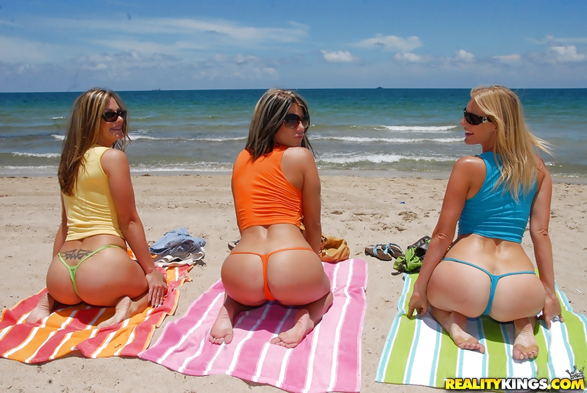 Busty women are sunbathing on the beach and having sex