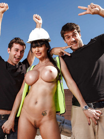 Powerful men are enjoying wild threesome with this busty builder in green uniform. She is being fucked with their cocks on the black sofa.