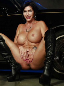 Slutty MILF with short dark hair is looking like a whore wearing black boots and the short red dress. She is fucking with her lover next to his car.