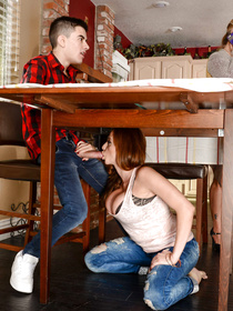 Redhead in pink panties masturbates and gets skull-fucked by a big-dicked younger dude after playing footsie with him, under the table.