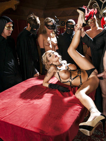 Sexy blonde in the mask is taking part in sensational orgy. She is sucking his big boner and getting fucked on the red table extremely hard.