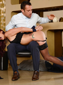 Ginger slut is getting spanked and fucked by her strong lover. She is enjoying wild sex with him on the black chair and on the white table.