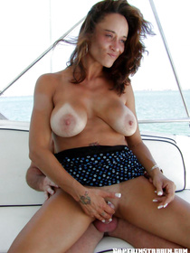 Upskirt shots reveal wonderful big tits of a beautiful lady while she is in her sexy dress on her lovers boat, getting ready for a great fuck.